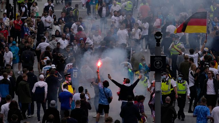 A supporter holds a flare at Wembley Way. Pic: AP