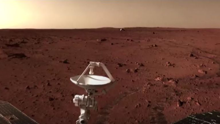 Another image of rover on the Martian surface with the lander in the background