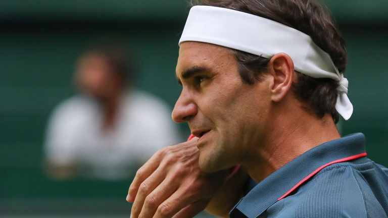 Roger Federer wipes his face during his ATP Tour Singles, Men, Round of 16 tennis match against Canada's Felix Auger-Aliassime in Halle, Germany, Wednesday, June 16, 2021. (Friso Gentsch/dpa via AP)
