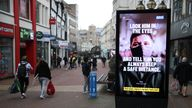 People make their way past a government coronavirus sign on Old Christchurch road in Bournemouth, Dorset, during England's third national lockdown to curb the spread of coronavirus. Picture date: Tuesday February 16, 2021.