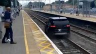 Stunned commuters watched as the car was driven along the tracks
