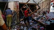 People pick up debris at the site of an explosion in Sadr City district of Baghdad, Iraq July 19, 2021. REUTERS/Wissam Al-Okaili