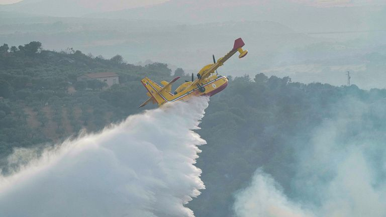A Canadair plane drops water to put out a fire, near Oristano, on the island of Sardinia, Italy, Monday, July 26, 2021. Fires raged Sunday on Italy's Mediterranean island of Sardinia, where nearly 400 people were evacuated overnight. No deaths or injuries have been reported. Firefighters said several homes were damaged in the island's western interior region. (Alessandro Tocco/LaPresse via AP)