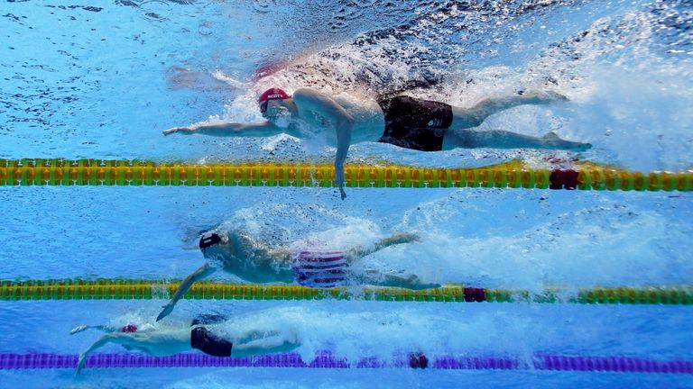 Britain's Duncan Scott, top, swims to win the silver medal in the 200-meter freestyle final at the 2020 Summer Olympics, Tuesday, July 27, 2021, in Tokyo. (AP Photo/David J. Phillip)