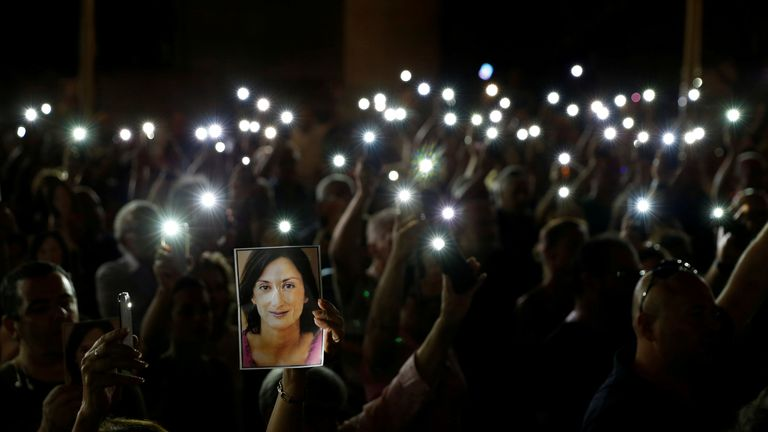 People hold up photos of assassinated anti-corruption journalist Daphne Caruana Galizia and torches on mobile phones during a vigil to mark eleven months since her murder in a car bomb, in Valletta, Malta September 16, 2018. REUTERS/Darrin Zammit Lupi TPX IMAGES OF THE DAY