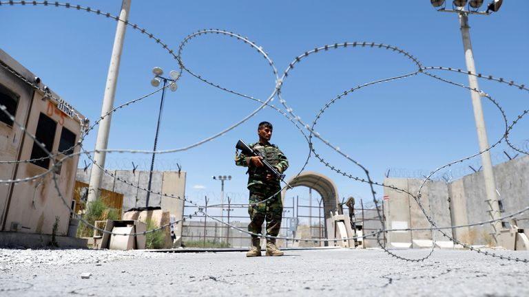 An Afghan soldier stands guard at Bagram airbase as the last US troops pulled out