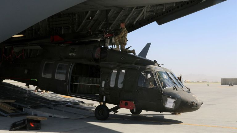 Aerial porters work with maintainers to load a UH-60L Blackhawk helicopter into a U.S. Air Force C-17 Globemaster III