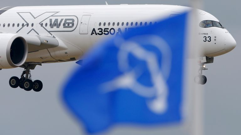 An Airbus A350 flies over a Boeing flag while landing after a flying display during the 51st Paris Air Show at Le Bourget airport near Paris, June 18, 2015