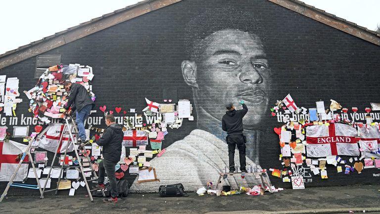 Street artist Akse P19 repairs the mural of Manchester United striker Marcus Rashford