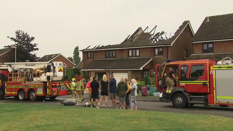 Neighbours look on as firefighters assess the damage