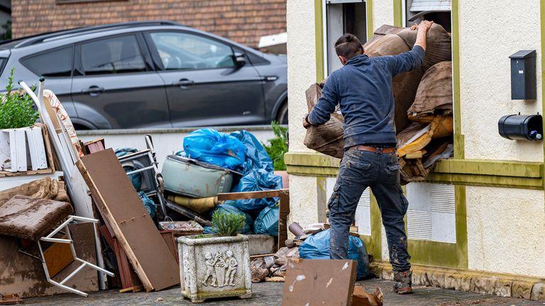 After flooding near Arloff, a man clears wet furniture through a window onto the street. Pic: Associated Press