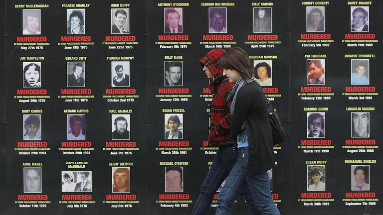 Two women walk past mural depicting victims of the troubles in west Belfast as talks continue on transferring policing and justice powers from London to Belfast