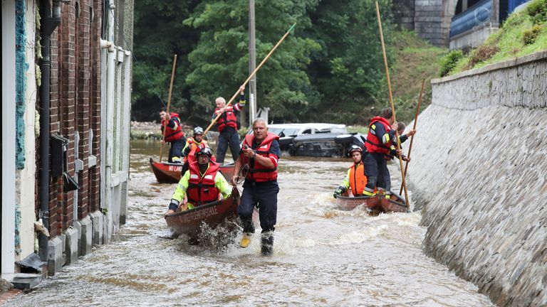 Austrian rescue team members use boats as they go through a flooded street in an area affected by floods, following heavy rainfalls, in Pepinster, Belgium, July 16, 2021. REUTERS/Yves Herman