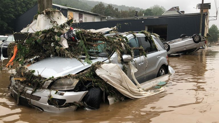 Damaged cars and debris in a flooded street in Pepinster, Belgium
