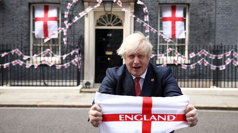 Britain's Boris Johnson poses on Downing Street with a flag ahead of the Euro 2020 final, in London, Britain July 9, 2021. REUTERS/Henry Nicholls