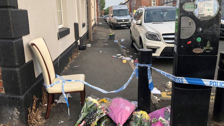 Flowers are left at the crime scene where a 31-year-old woman suffered severe burns and later died