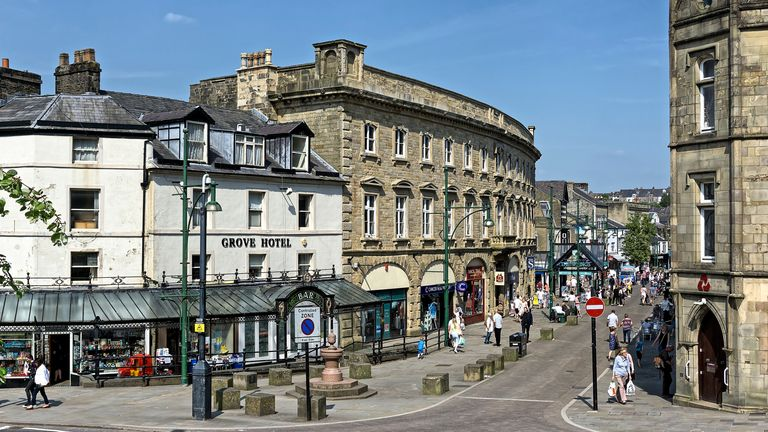 View of Buxton town centre, Derbyshire, UK.  Shops can be seen on the far side of the road and people can be seen waking on the pavements.