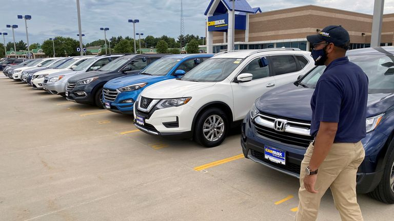 """Brandon Parrum, general manager of CarMax's Des Moines store, walks past some of the many vehicles that customers can arrange to buy online and collect at the store using """"contactless"""" curbside pickup, a service the U.S. used car retailer launched during the coronavirus disease (COVID-19) pandemic, in De Moines, Iowa, U.S. July 29, 2020."""
