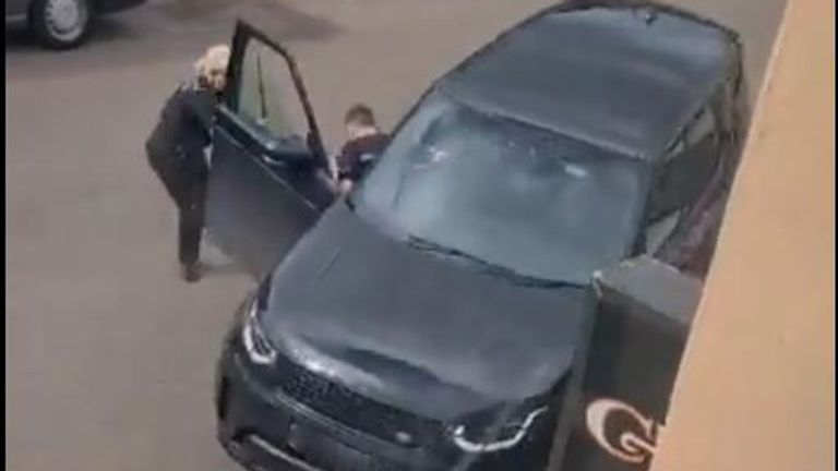 The male officer got dragged along as the car was reversed