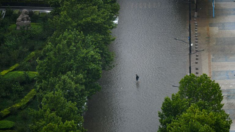 20 يوليو 2021 رجل يسير في شلال مياه الأمطار في مدينة تشنغتشو بمقاطعة خنان بوسط الصين.  (ImagineChina عبر AB Images)
