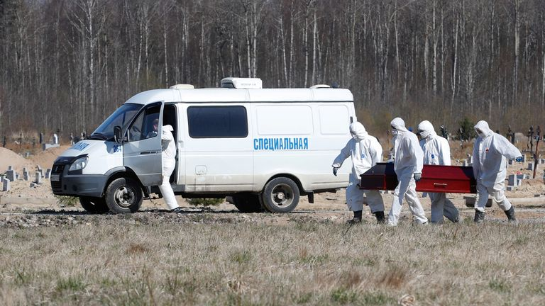Gravediggers carry a COVID-19 victim at a special purpose section of a graveyard on the outskirts of Saint Petersburg