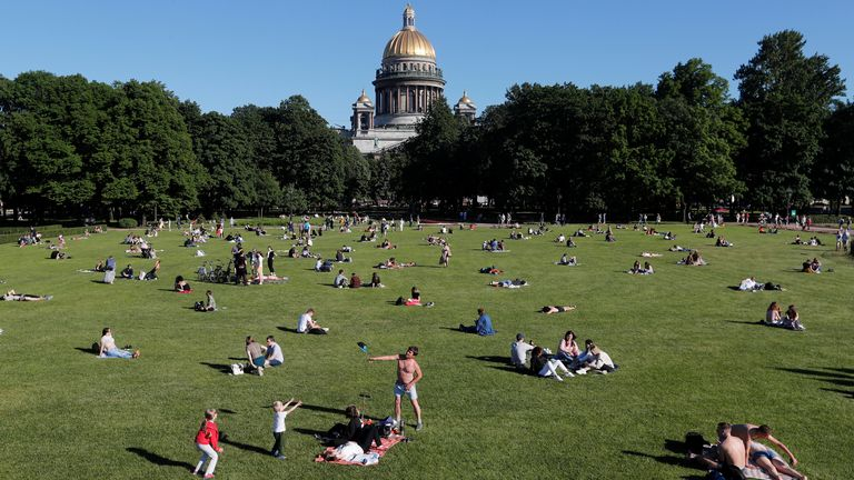 People maintain social distance at a park next to St Isaac's Cathedral in Saint Petersburg