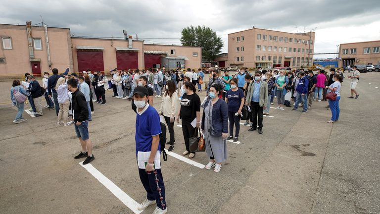 Migrant workers stand in a queue to receive the one-dose Sputnik Light vaccine in Moscow