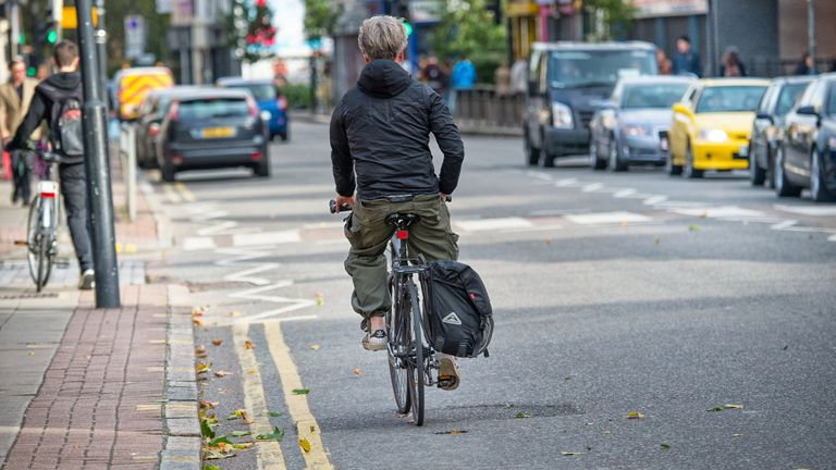 London, UK - October 27, 2013: Rear view of bicyclist. Street scene in central London. Car queue and traffic in background.