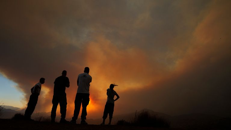 Residents of villages watch a fire in the Larnaca mountain region on Saturday, July 3, 2021. Cyprus has asked fellow European Union member states on Saturday to help battle a huge fire in a mountainous region of the east Mediterranean island nation that has forced the evacuation of at least three villages. (AP Photo/Petros Karadjias)