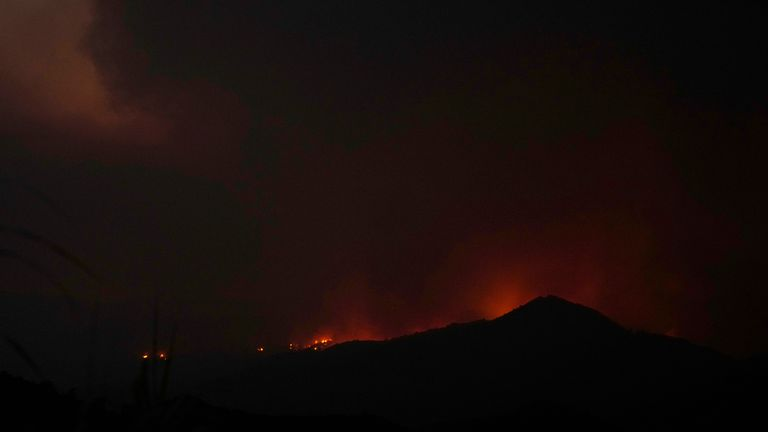 Fire on a mountain as a smoke is seen on the sky at Larnaca mountain region on Saturday, July 3, 2021. Cyprus has asked fellow European Union member states on Saturday to help battle a huge fire in a mountainous region of the east Mediterranean island nation that has forced the evacuation of at least three villages. (AP Photo/Petros Karadjias)