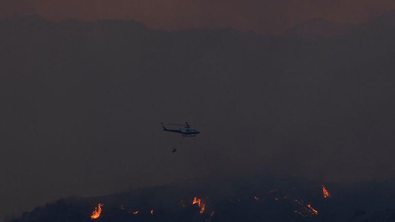 Un elicottero sorvola un incendio boschivo nella regione montuosa di Larnaca, sabato 3 luglio 2021. Cipro ha chiesto ai paesi dell'Unione europea di aiutare a combattere un enorme incendio in una regione montuosa del paese del Mediterraneo orientale che ha costretto almeno tre villaggi .  Il ministro dell'ambiente cipriota Costas Kadis ha detto alla stazione televisiva ufficiale Satordasi che l'incendio aveva causato