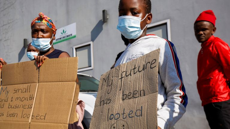 People stand with placards as Cyril Ramaphosa visited a Durban shopping centre damaged in the riots that followed the imprisonment of former leader Jacob Zuma