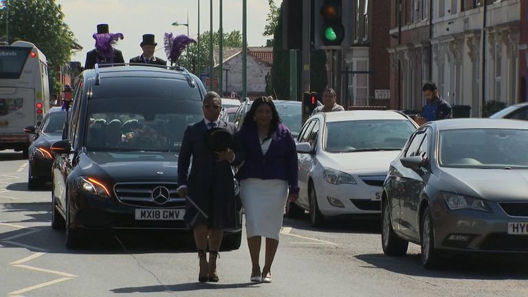 Dea-John's mother leads the funeral procession