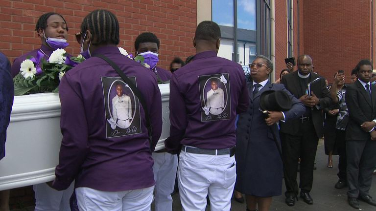 Family members and friends carry Dea-John's coffin