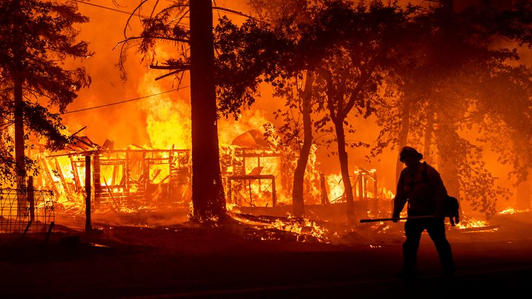 A firefighter passes a burning home during the Dixie fire in Plumas County, California. Pic: AP