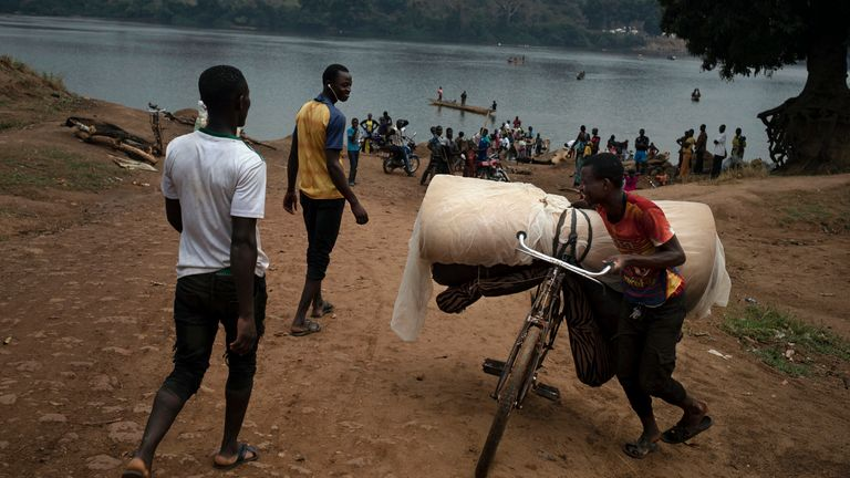 Jeremy Kowomando, 32, and his 14-large family, cross the Mbomou river back into Bangassou, Central African Republic, from Ndu in the Democratic Republic of the Congo, where they had taken refuge, Sunday Feb. 14, 2021. ...For more than a month we received no aid,... says Kowomando, explaining why he was returning. An estimated 240,000 people have been displaced in the country since mid-December, according to U.N. relief workers, when rebels calling themselves the Coalition of Patriots for Change launched attacks, causing a humanitarian crisis in the already unstable nation. (AP Photo/Adrienne Surprenant)