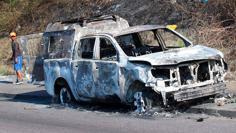 A pedestrian passes a burnt out vehicle in Durban. Pic: AP