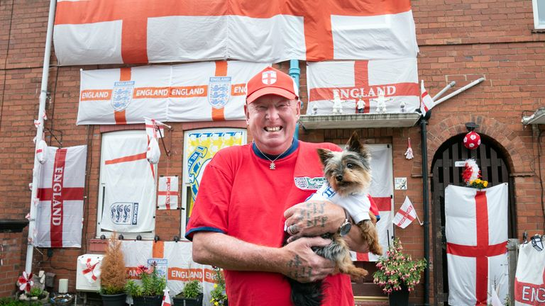 Benny Elcock, with his dog Reggie, stands in front of his house in York, Yorkshire