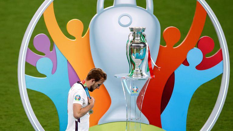 A dejected Harry Kane walks past the Euro 2020 trophy