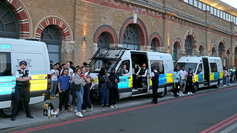 Fans and Police vans outside the Vinegar Yard in London watching the Euro 2020 semi final match between England and Denmark. Picture date: Wednesday July 7, 2021.