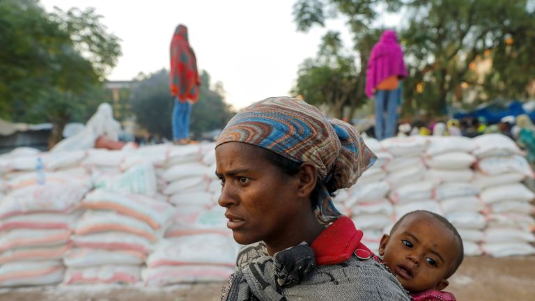 A woman carries an infant as she queues in line for food
