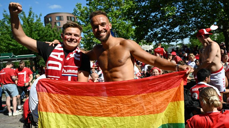 Denmark fans pose in Copenhagen with a rainbow coloured flag before the match