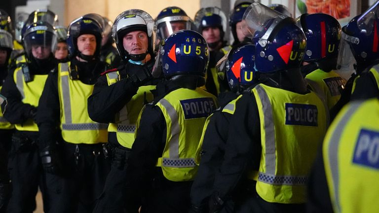 Riot police observe England fans celebrating in Piccadilly Circus, central London, after England qualified for the Euro 2020 final, winning their semi final match against Denmark. Picture date: Wednesday July 7, 2021.