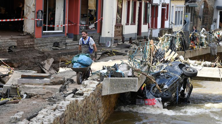 dpatop - 17 July 2021, North Rhine-Westphalia, Bad M..nstereifel: A helper carries rubbish and debris along the Erft. In the night of 15.07.2021, the Erft floods totally devastated the historic core of the city. Streets and shops were flooded. Gas, electricity and telephone lines were exposed. Photo: Roberto Pfeil/dpa