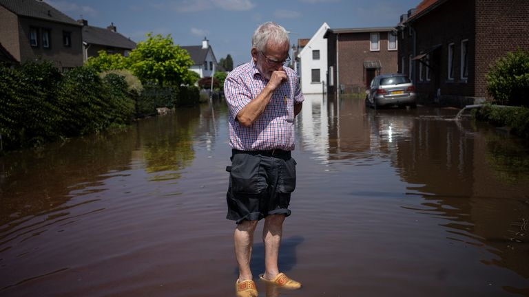 Wiel de Bie, 75, stands outside his flooded home in the town of Brommelen, Netherlands, Saturday, July 17, 2021. In the southern Dutch province of Limburg, which also has been hit hard by flooding, troops piled sandbags to strengthen a 1.1-kilometer (0.7 mile) stretch of dike along the Maas River, and police helped evacuate low-lying neighborhoods. (AP Photo/Bram Janssen)