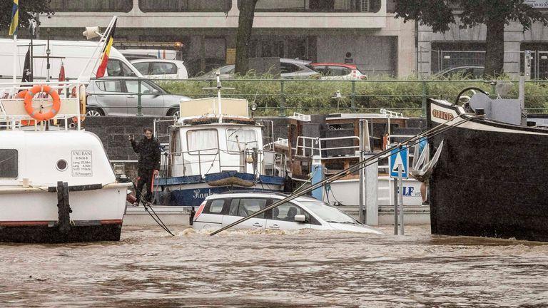 Un'auto è sommersa tra due barche nel fiume Mosa durante un'inondazione a Liegi, in Belgio.  Pic: AP