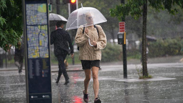 A person walks through a heavy downpour in Euston, London