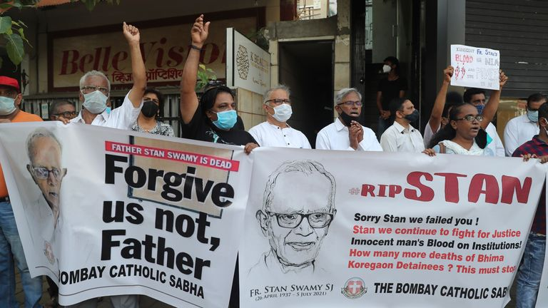 People hold banners and shout slogans during a prayer meeting for Father Stan Swam. Pic: AP
