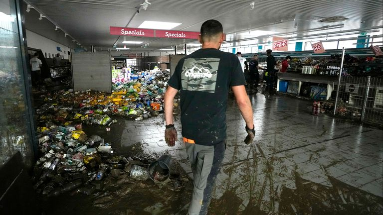 A worker cleans out items from a supermarket after flooding in Pepinster, Belgium, Saturday, July 17, 2021. Residents in several provinces were cleaning up after severe flooding in Germany and Belgium turned streams and streets into raging torrents that swept away cars and caused houses to collapse. (AP Photo/Virginia Mayo)