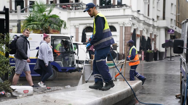 Workers continue to clean Leicester Square at in central London on Monday morning